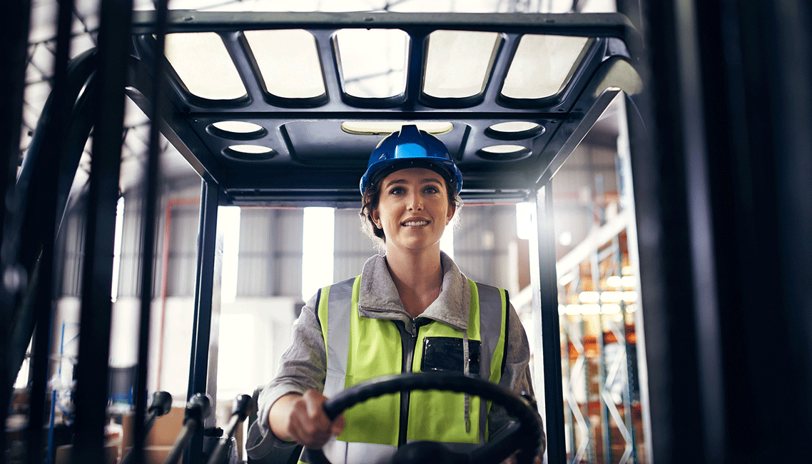 A woman driving a fork lift with a determined look on her face.